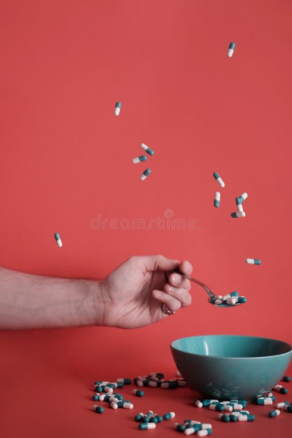 Männliche Hand fängt die Pille mit einem Löffel Platte und zerstreute Tabletten herum mit einem leeren Raum lizenzfreies stockbild