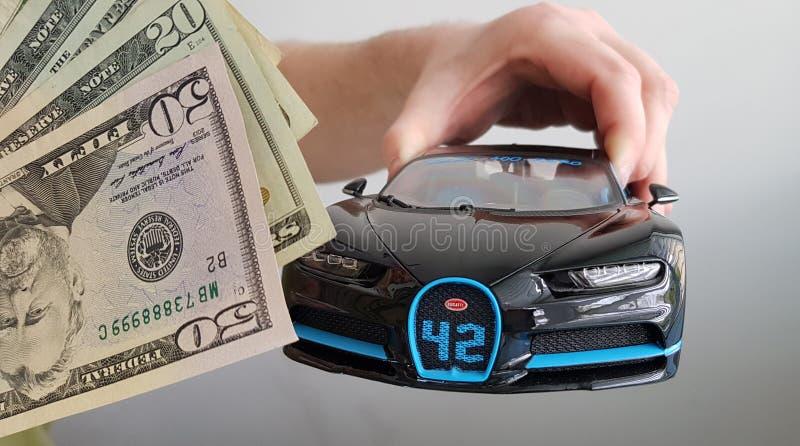 Männliche Handholding im Luft schwarzen Auto-Metallspielzeug Bugattis Chiron auf weißem Hintergrund lizenzfreie stockfotos
