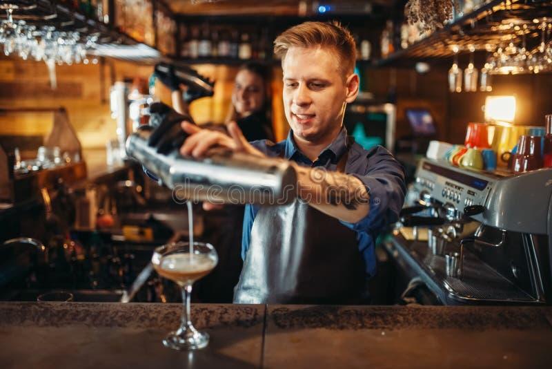 Männlicher Kellner, der das Getränk vom Schüttel-Apparat gießt stockbilder