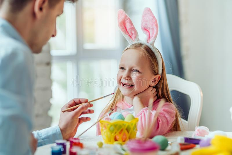 Mój tata jest najlepszy w świacie! Tata i jego mała córka wpólnie zabawę podczas gdy przygotowywający dla Wielkanocnych wakacji zdjęcia stock