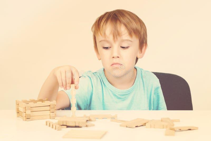Müder Schüler über weißem Hintergrund Trauriger oder gebohrter Junge mit harter schwieriger Aufgabe Hölzerne Strukturprobleme Frü stockfotos