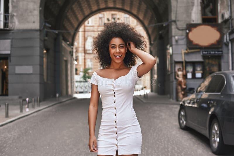 Mühelose Schönheit Attraktive junge afroe-amerikanisch Frau im kurzen weißen Kleid, das mit dem Haar und dem Lächeln spielt lizenzfreie stockfotos
