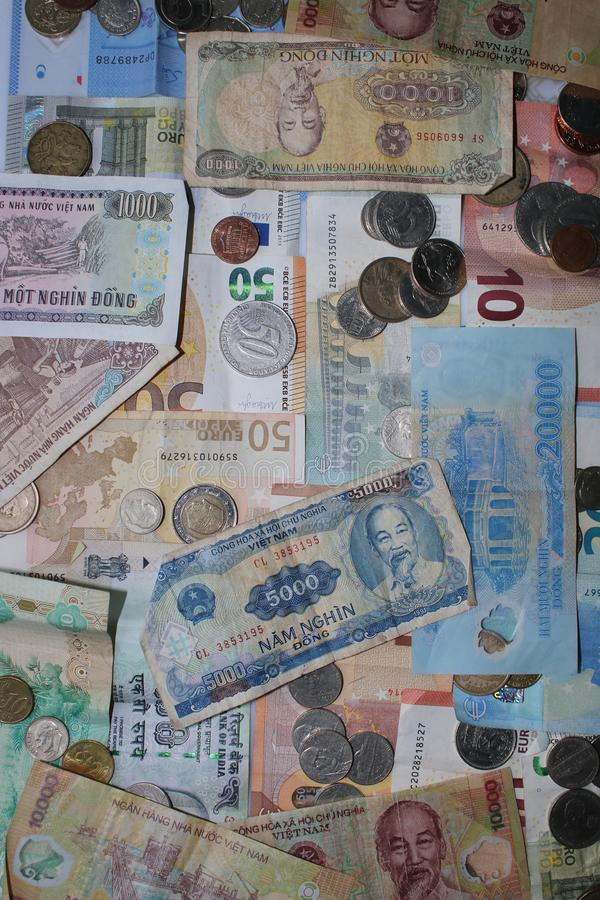 Münzen und Banknoten von vier verschiedenen Währungen - Europa, Vietnam, Großbritannien und Amerika stockfotografie