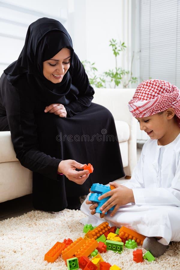 Mãe árabe e filho junto que jogam em casa com brinquedos fotografia de stock