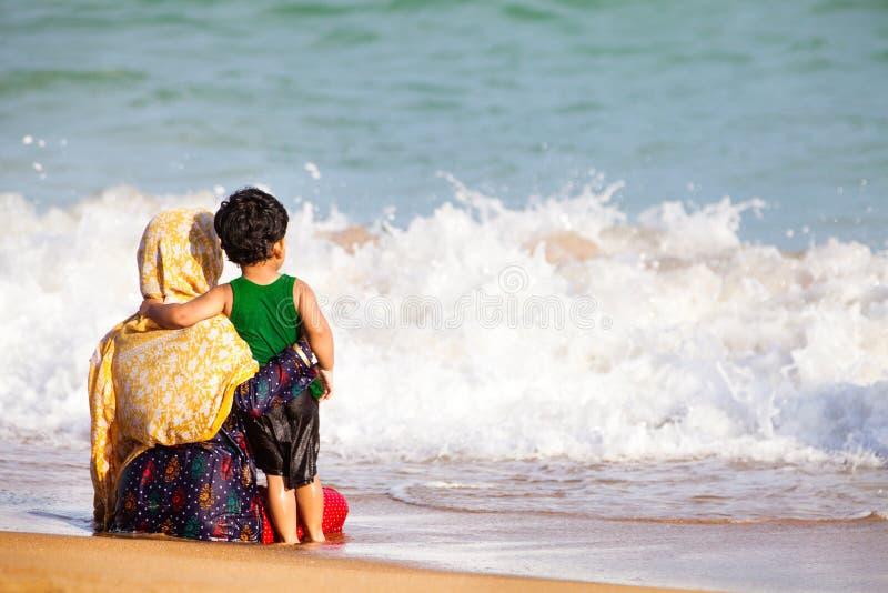 Mãe árabe e filho que abraçam ao mar
