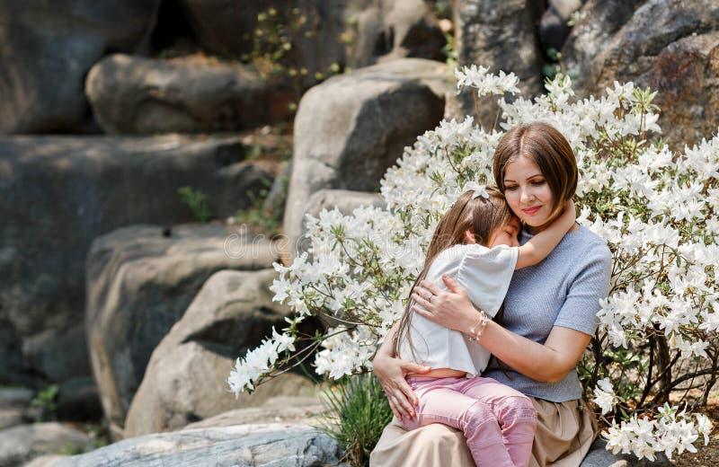 A mãe abraça a filha bonita da criança no campo de flores brancas Relacionamento de família e conceito do amor imagens de stock royalty free