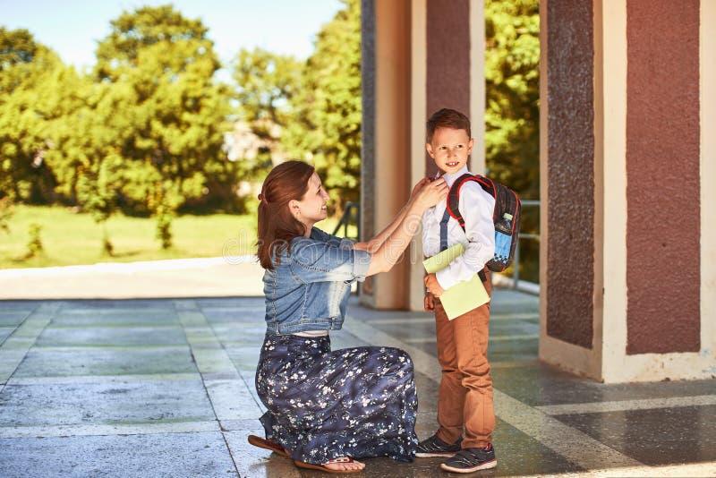 A mãe acompanha a criança à escola a mamã incentiva o estudante que acompanha o à escola uma mãe de inquietação olha maciamente n fotografia de stock royalty free