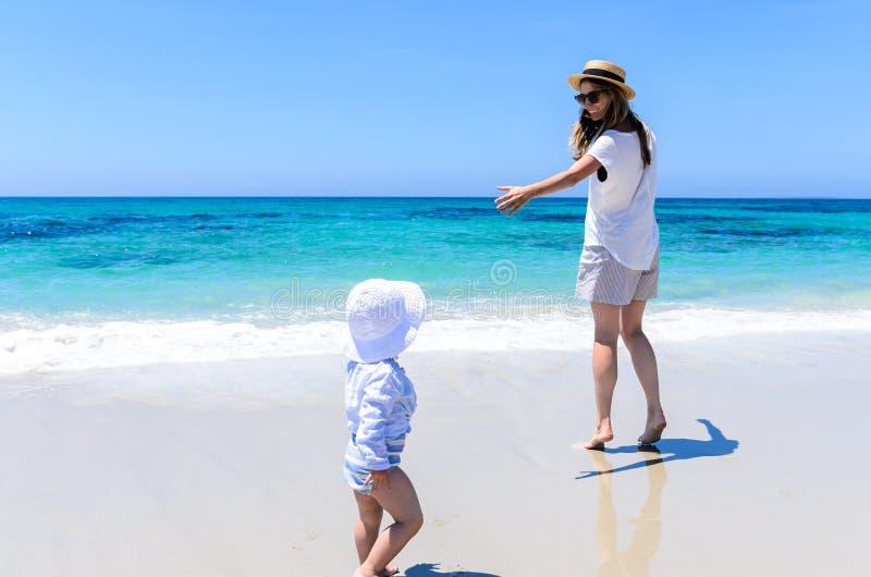 Mãe adorável nova que tem o divertimento com a filha pequena na praia tropical imagem de stock royalty free