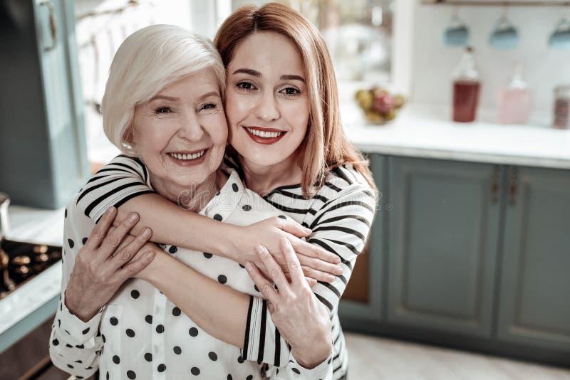 Mãe adulta e filha que sorriem e que sentem felizes ao abraçar imagem de stock