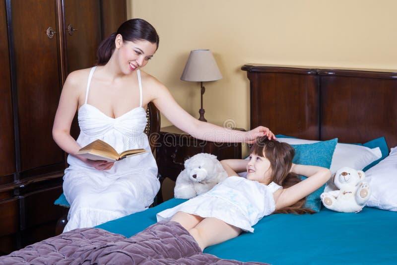 A mãe adulta ensina sua filha ler, tocando em sua cabeça imagem de stock