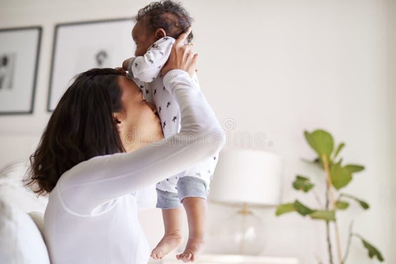 Mãe adulta nova afro-americano feliz que aumenta seu filho idoso do bebê de três meses no ar e que beija sua barriga, fim acima,  imagem de stock royalty free