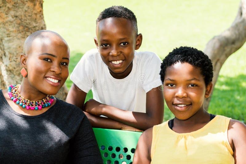 Mãe africana com duas crianças fora fotos de stock