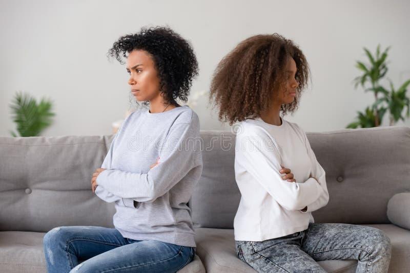Mãe africana da filha da família que senta-se no sofá separadamente após a discussão fotografia de stock