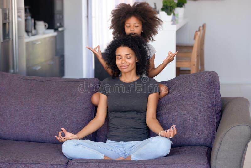 Mãe africana e filha pequena que meditam sobre o sofá em casa fotografia de stock