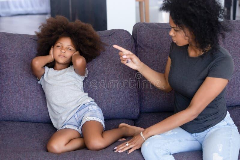 Mãe africana que discute a filha pequena que senta-se no sofá em casa foto de stock