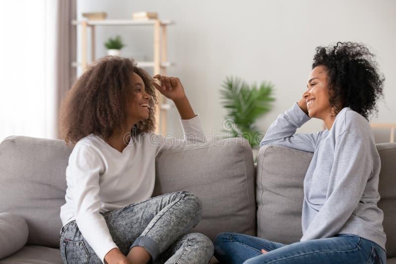 Mãe afro-americano feliz e filha adolescente que conversam em casa imagens de stock