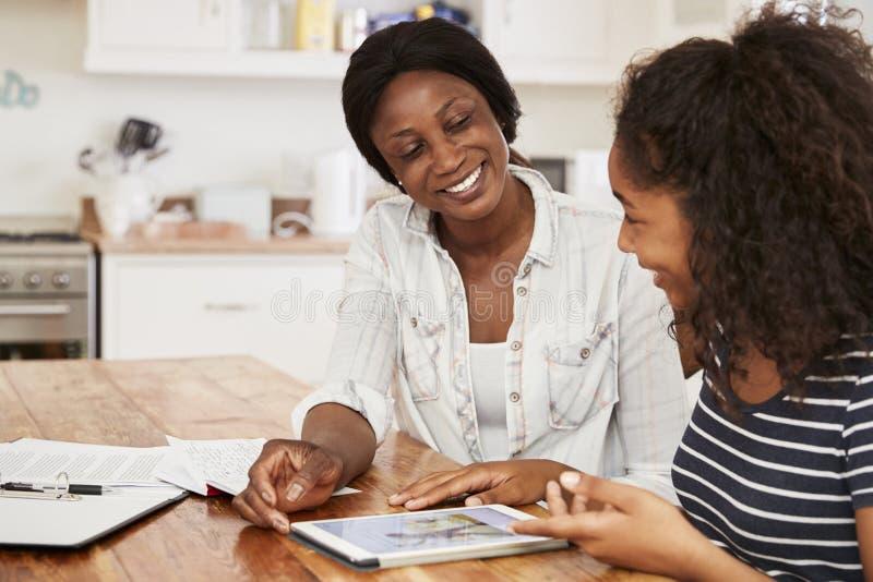 A mãe ajuda a filha adolescente com trabalhos de casa usando a tabuleta de Digitas fotografia de stock royalty free