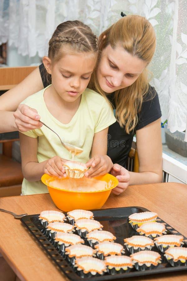 A mãe ajuda a filha a derramar a massa no molde para queques foto de stock