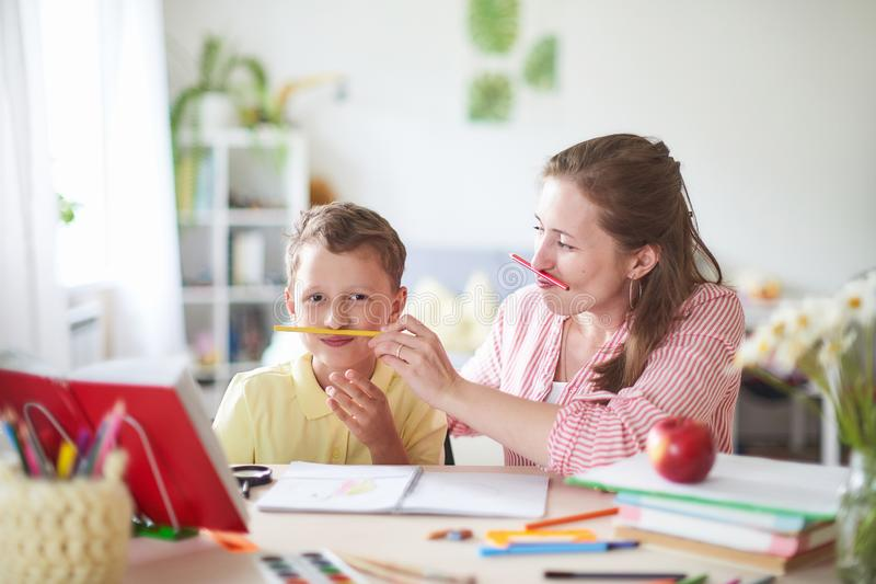 A mãe ajuda o filho a fazer lições educação de casa, lições da casa a mulher é contratada com a criança, verificações o trabalho  imagem de stock