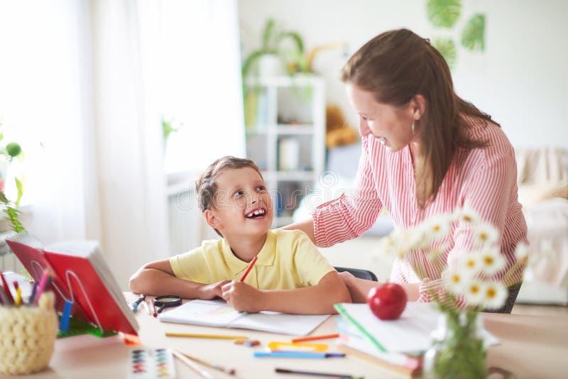 A mãe ajuda o filho a fazer lições educação de casa, lições da casa o tutor é contratado com a criança, ensina para escrever e co imagens de stock