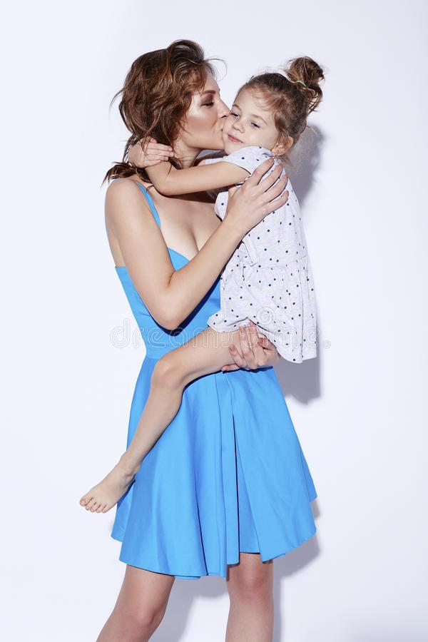 Mãe alegre de sorriso feliz nova que beija sua filha pequena adorável Conceito do março do dia da mãe imagens de stock royalty free