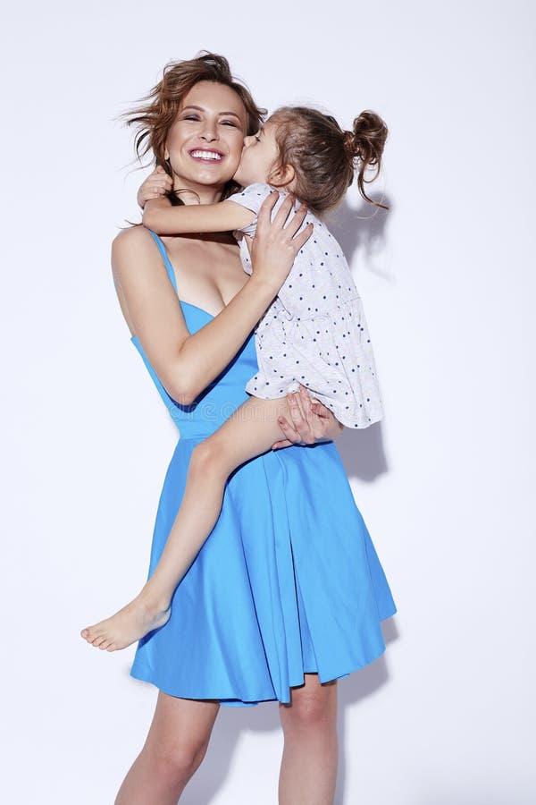 Mãe alegre de sorriso feliz nova que guarda sua filha pequena adorável Conceito do março do dia da mãe imagem de stock royalty free