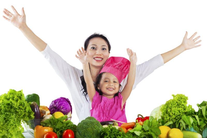 Mãe alegre e criança que cozinham vegetais foto de stock royalty free