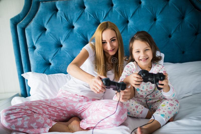 Mãe alegre e filha que jogam jogos de vídeo na cama em casa imagem de stock
