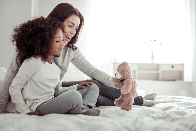 Mãe alegre e filha que jogam junto na sala fotografia de stock royalty free
