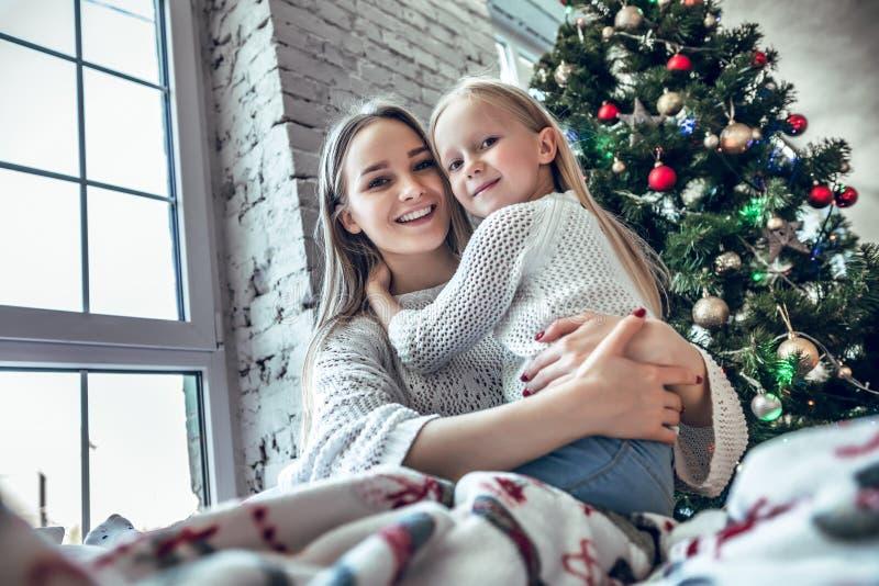 Mãe alegre e filha que sentam-se na cama perto da árvore de Natal decorada bonita fotos de stock