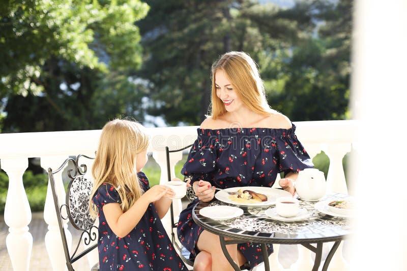 Mãe alegre e filha que sentam-se no café do ar livre quando drin foto de stock royalty free