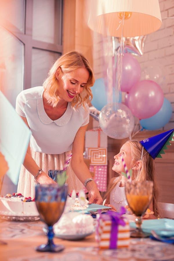 Mãe alegre que sorri ao pôr o bolo sobre a placa fotografia de stock