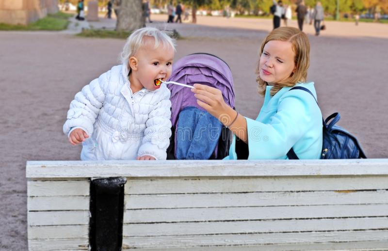 A mãe alimenta pouca filha no banco nos jardins fotografia de stock royalty free