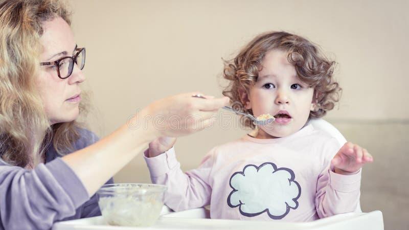 A mãe alimenta seu bebê bonito com uma colher imagens de stock