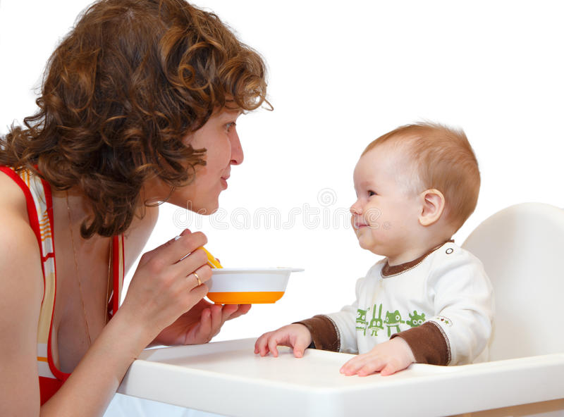 A mãe alimenta seu bebê pequeno fotos de stock royalty free