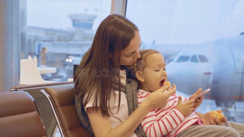 A mãe alimenta sua filha pequena com a tangerina no aeroporto fotos de stock royalty free