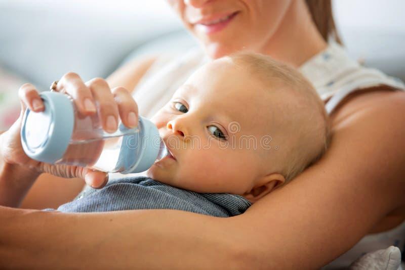 Mãe, alimentando seu bebê da garrafa, sentando-se no sofá a fotografia de stock
