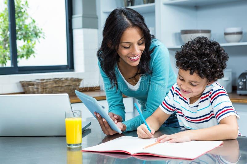 Mãe amável que ajuda seu filho que faz trabalhos de casa na cozinha imagens de stock