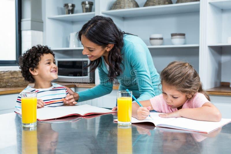 Mãe amável que ajuda suas crianças que fazem trabalhos de casa fotografia de stock royalty free