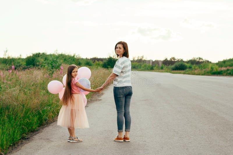 mãe amigável e filha da família que andam no por do sol foto de stock royalty free