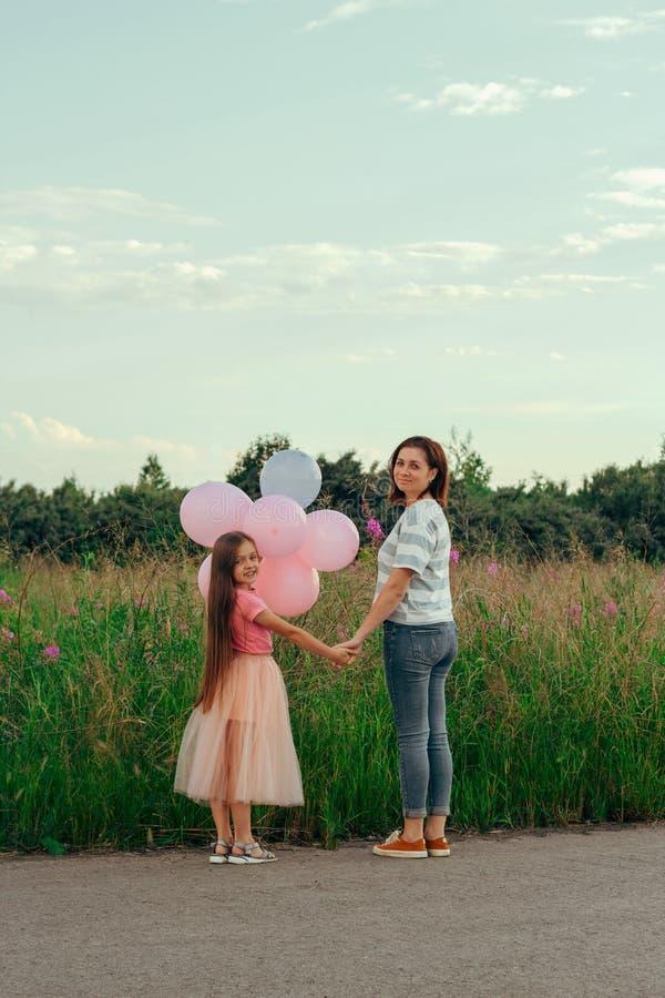 mãe amigável e filha da família que andam no por do sol imagens de stock royalty free