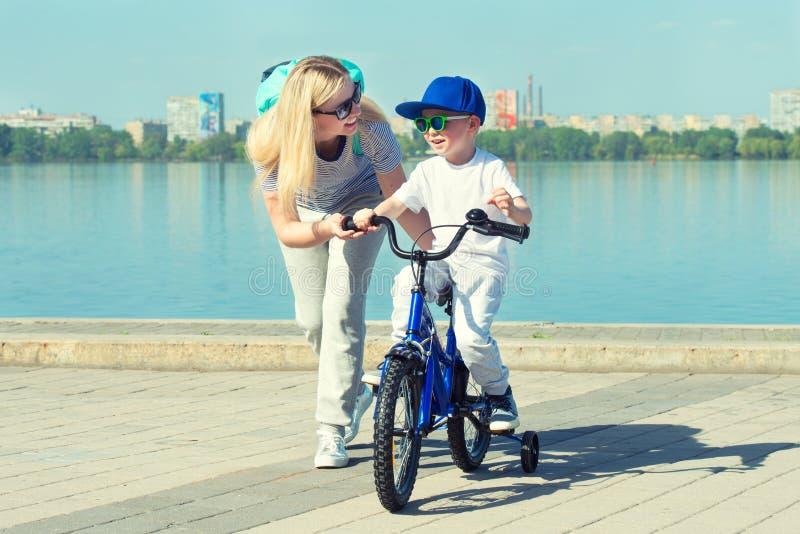 A mãe aprende seu filho pequeno montar uma bicicleta fotografia de stock