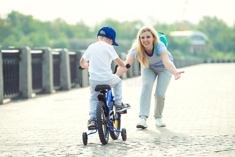 A mãe aprende seu filho pequeno montar uma bicicleta imagens de stock royalty free