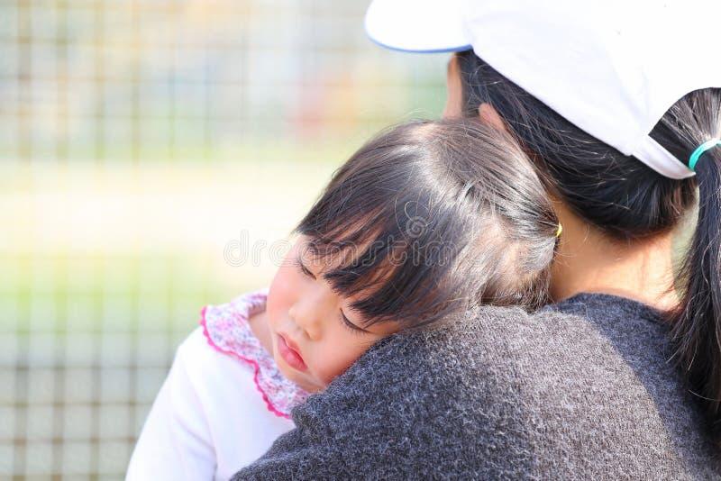 A mãe ascendente próxima leva a menina da criança em seus braços imagens de stock royalty free