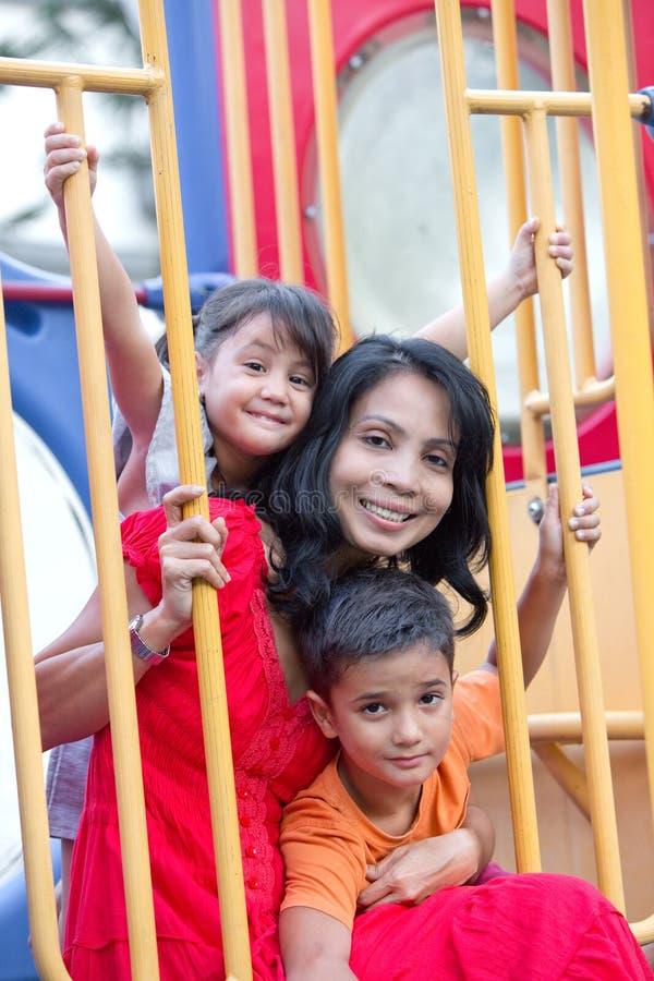 Mãe asiática com as duas jovens crianças no campo de jogos fotos de stock royalty free