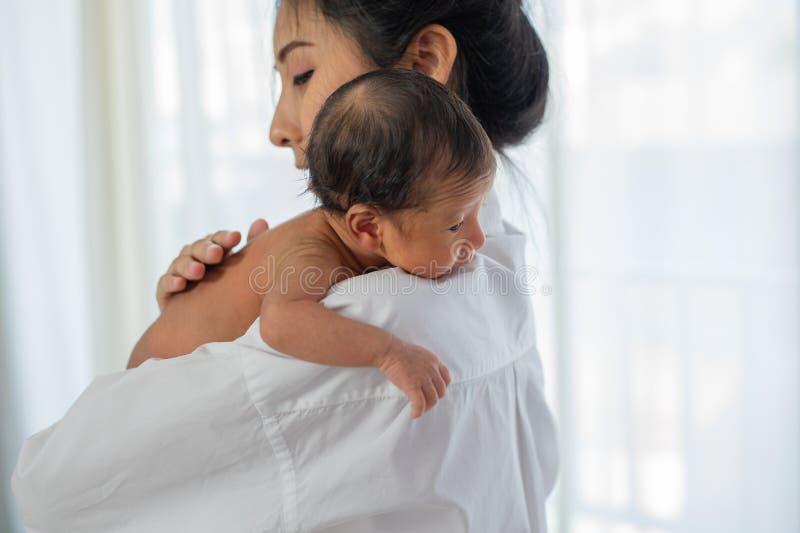 A mãe asiática com lugar branco da camisa em cima do ombro de pouco bebê recém-nascido após dá o leite e o bebê olha sonolento fotografia de stock
