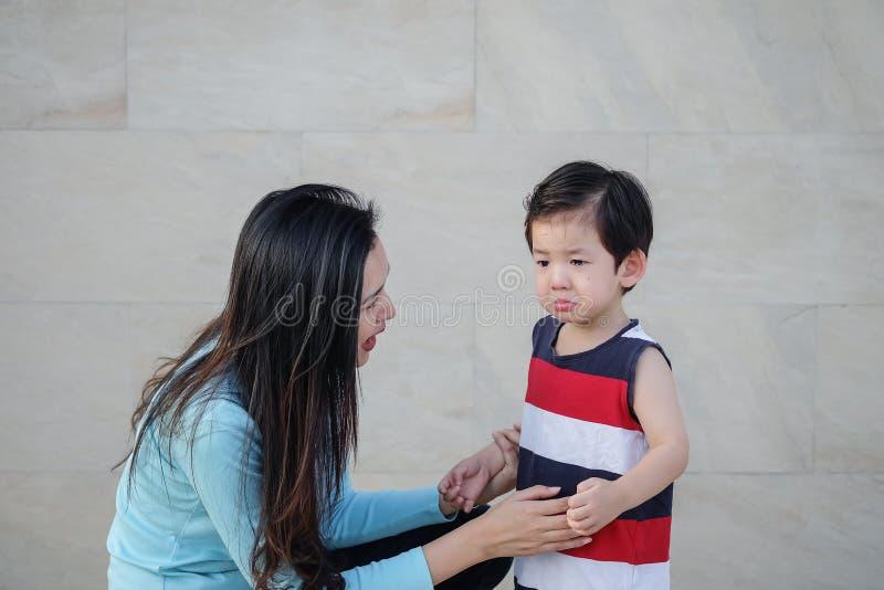 A mãe asiática do close up está consolando seu filho de grito no fundo textured de mármore da parede de pedra fotografia de stock royalty free