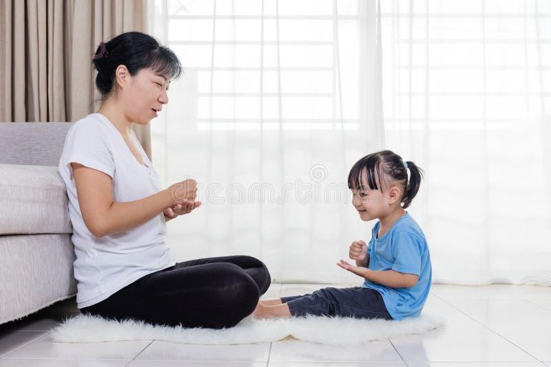 Mãe asiática e filha chinesas que jogam rocha-papel-tesouras fotografia de stock
