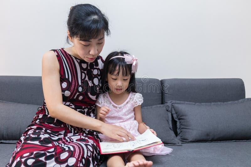 Mãe asiática e filha chinesas que leem o livro no sofá fotografia de stock royalty free