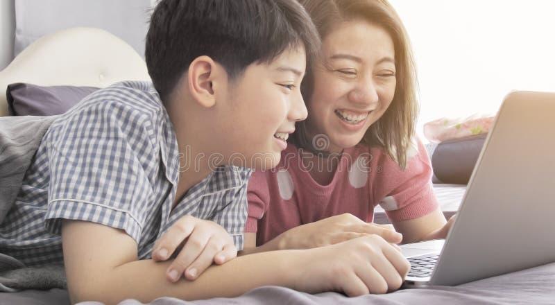 Mãe asiática e filho da família que olham no laptop foto de stock royalty free